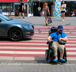 man in a wheelchair at a pedestrian crossing
