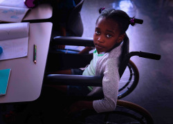 Schoolgirl looking at camera and sitting at desk in classroom of elementary school