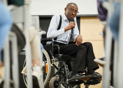 speaker in wheelchair speaking at conference