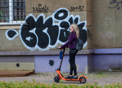 Young woman with headphones riding with electric scooter on pavement in the city.