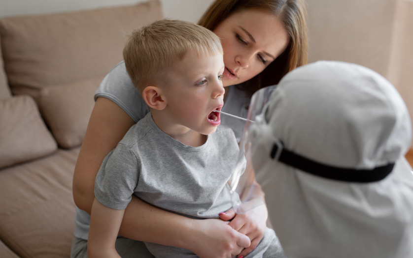 Doctor takes a cotton bud from child's mouth to analyze the saliva for coronavirus
