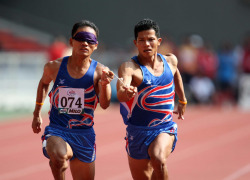 Thailand's blind athlete Kitsana Jorchuy runs with a guide at the track and field event of the fifth ASEAN Para Games on August 15, 2009 in Kuala Lumpur.