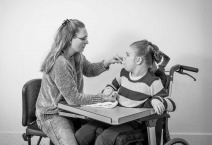 A disabled child in a wheelchair being cared for by a voluntary care worker.