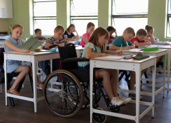 Side view of a diverse group of schoolchildren sitting at desks in classroom, with one schoolgirl sitting in a wheelchair