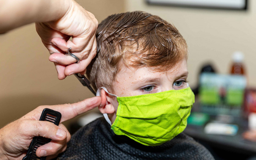 little boy getting hair cut at the barbershop wearing protective mask