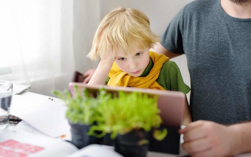 Father helping son with disability studying homework