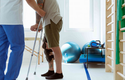 Injured patient learns to walk on crutches in medical office