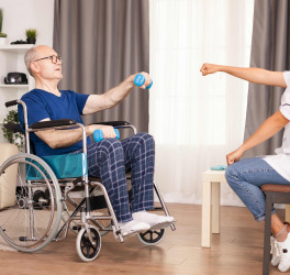 old man in wheelchair with medical worker in nursing care home assistance