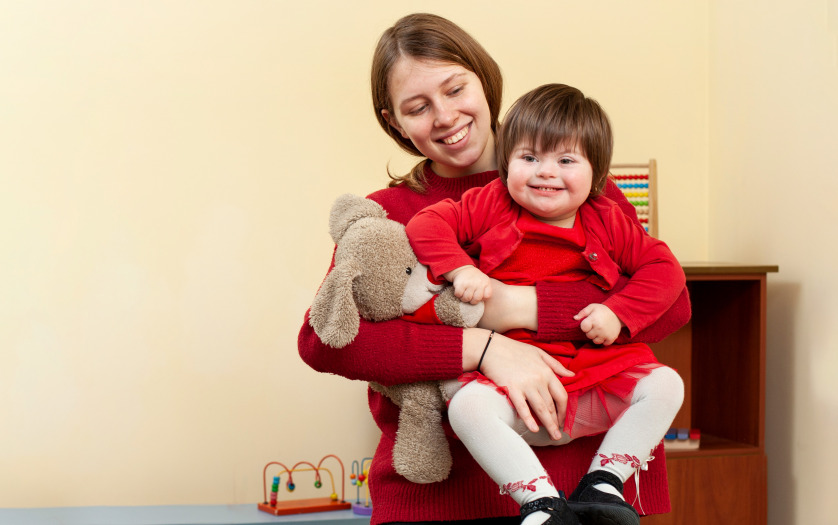 Woman holding smiley child with down syndrome