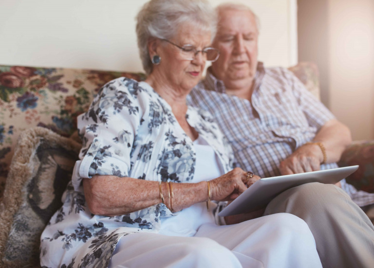 old woman sitting with her husband and using digital tablet.
