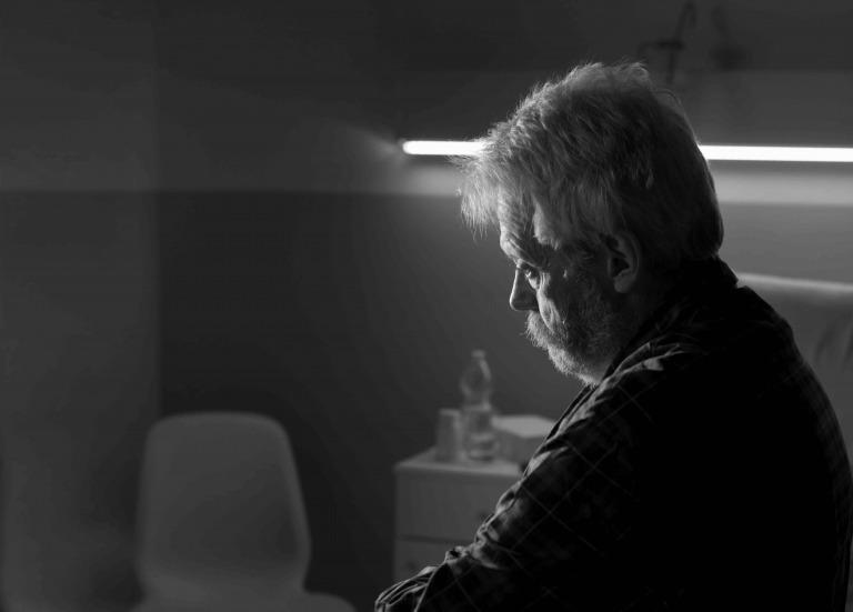 senior man sitting on the hospital bed alone at night