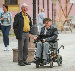 Close up of two senior men while one is in the wheelchairs and driving in the street of Vinkovci, Croatia.