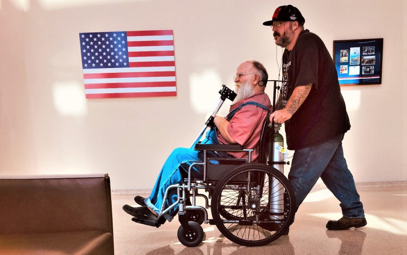 Young man pushing his father in wheelchair