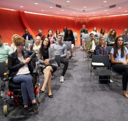 Students sit facing camera in a modern university classroom