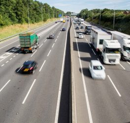 An aerial view of a busy UK motorway or highway with speeding cars and traffic and copy space