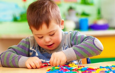 Cute kid boy with down`s syndrome playing in kindergarten