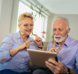 Smiling deaf senior couple talking using sign language on the digital tablet's cam