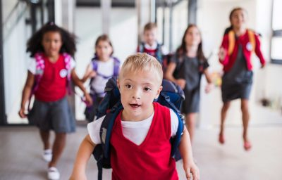 A down-syndrome school boy with bag and group of children in corridor, running.