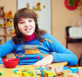 Portrait of happy kid with disability develops fine motor skills at rehabilitation center
