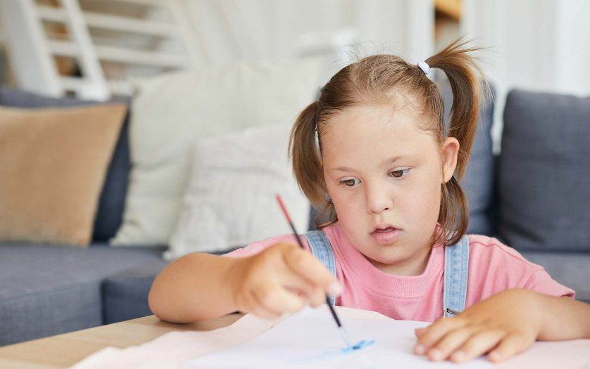 Little girl with down syndrome learning to paint with paints at the table at home