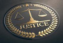 Scales of justice embossed symbol design with golden foil over black paper background.