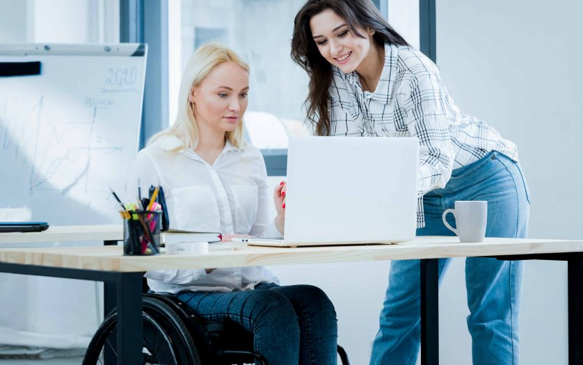 Front view of woman in wheelchair working at desk