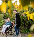 woman in wheelchair with assistant in garden