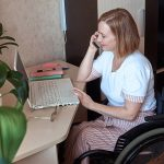 A female freelancer in a wheelchair, works remotely from home