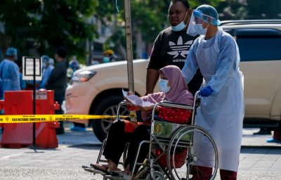 Medical personnel helps a woman in wheelchair to do the COVID-19 test to taking nasal and mouth swab at Kampung Baru.