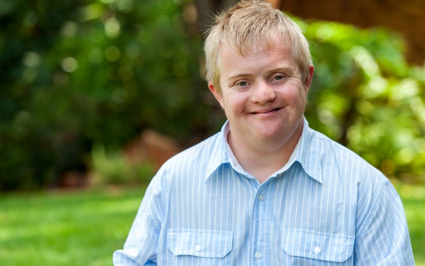 Portrait of handsome boy with Down syndrome in blue shirt outdoors.