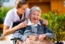 Senior women at home with nurse in garden sitting in wheelchair