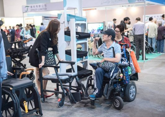 a wheelchair user speaking to the exhibitor