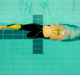 A female multi disability swimmer jumps off the starting blocks