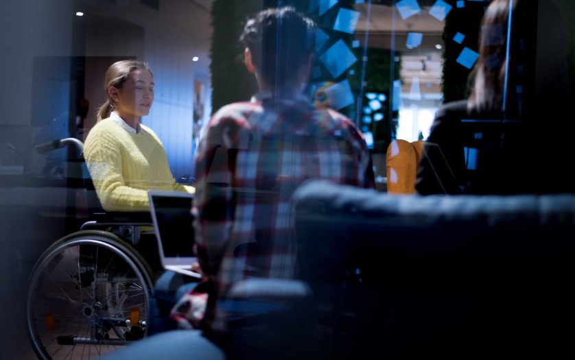 young woman in wheelchair with colleagues working in office