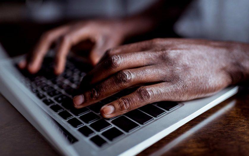 cropped shot of african-american man typing on laptop