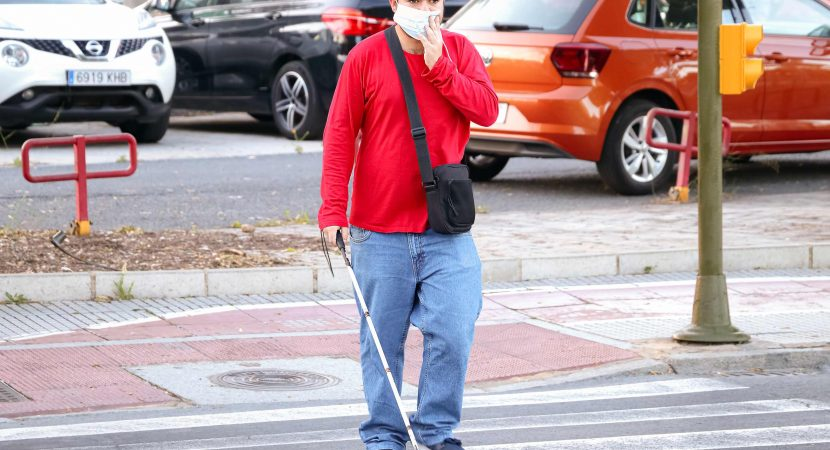 Blind person with white stick walking on street and crossing a crosswalk.