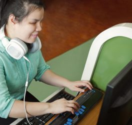 young blind woman with headphone using computer with refreshable braille display