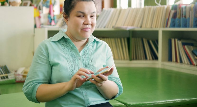 blind woman using smart phone with voice accessibility for persons with disabilities