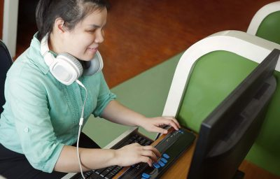 young blind woman with headphone using computer with refreshable braille display or braille terminal a technology device for persons with visual disabilities.