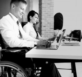 Businessman in a wheelchair working at a laptop