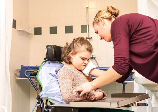 girl in a wheelchair being cared for by a carer in a specially adapted bathroom