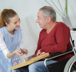 Photo of happy elderly men with disability and helpful nurse