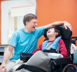 Father talking with son sitting in wheelchair while waiting in doctor s office, laughing together.