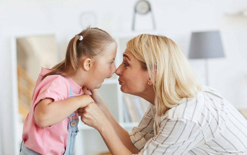 Girl with down syndrome and her mother looking at each other face to face they playing at home