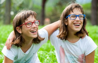 Close up portrait of two disabled twin sisters laughing outdoors.