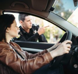 Male cop in uniform shows the way to female driver