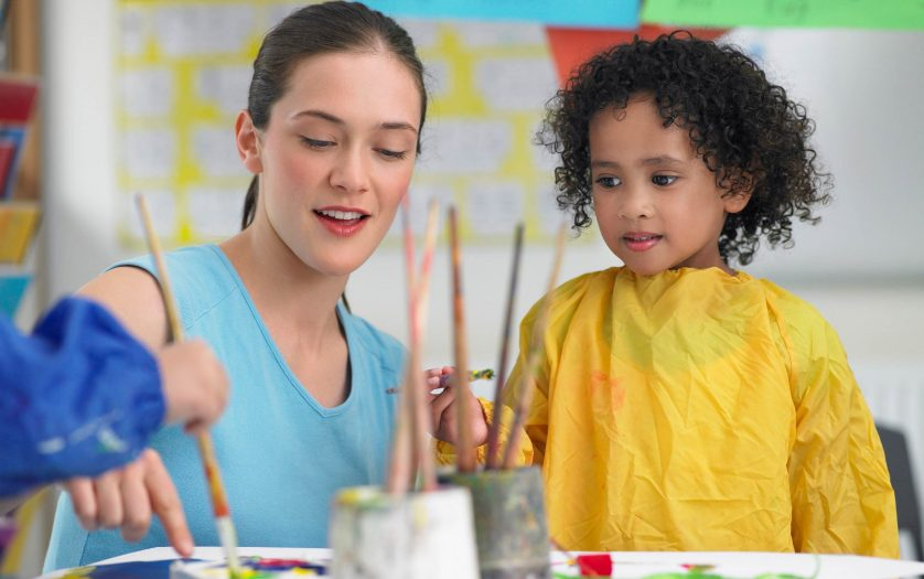 Young teacher assisting cute girl in painting during art class