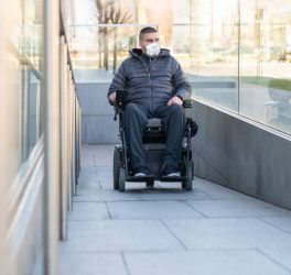 Disabled man on wheelchair wearing medical face mask for coronavirus protection.
