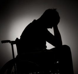 Sad man sitting on wheelchair in empty room