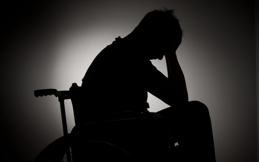Sad man sitting on wheelchair in empty room